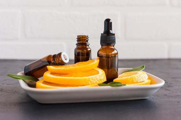 Cosmetische sinaasappelolie in een fles met een druppelaar en twee flessen etherische olie tegen de achtergrond van stukjes sinaasappel.