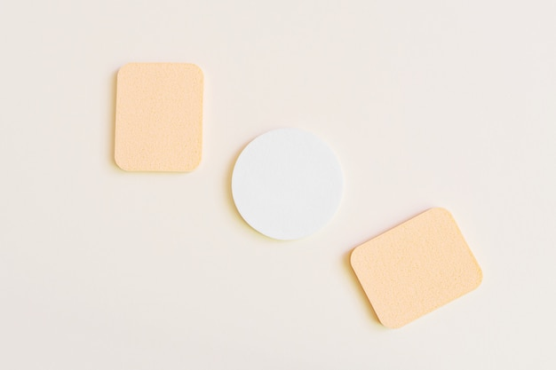 Cosmetische sponzen op een beige kleur. het concept van gezichts- en lichaamsverzorging, cosmetologie. minimalisme, bovenaanzicht. copyspace