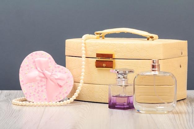Cosmetische tas, flessen parfum en geschenkdoos in hart scherp op houten planken en grijze achtergrond. viering dag concept.