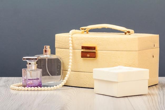 Cosmetische tas, flessen parfum en geschenkdoos op houten planken en grijze achtergrond. viering dag concept.