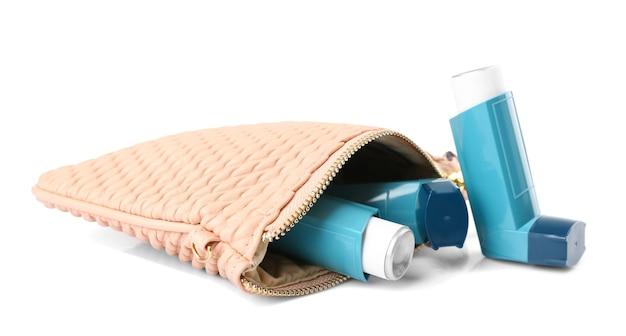 Cosmetische tas met astma-inhalatoren op wit oppervlak
