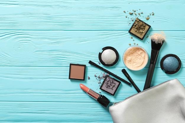 Cosmetische tas met decoratieve cosmetica op een blauwe achtergrond. plaats voor tekst. detailopname