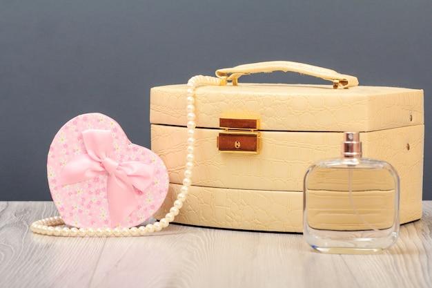 Cosmetische tas, parfum en geschenkdoos in hart scherp op houten planken en grijze achtergrond. viering dag concept.