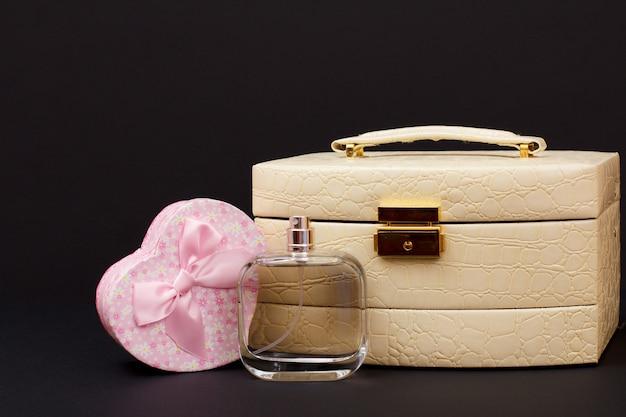 Cosmetische tas, parfum en geschenkdoos in hartvorm op zwarte achtergrond. viering dag concept.