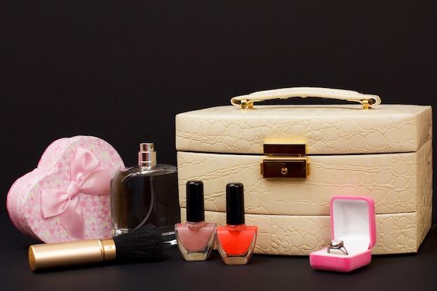 Cosmetische tas, parfum, nagellak, doos met een ring, borstel en geschenkdoos in hartvorm op zwarte achtergrond. viering dag concept.