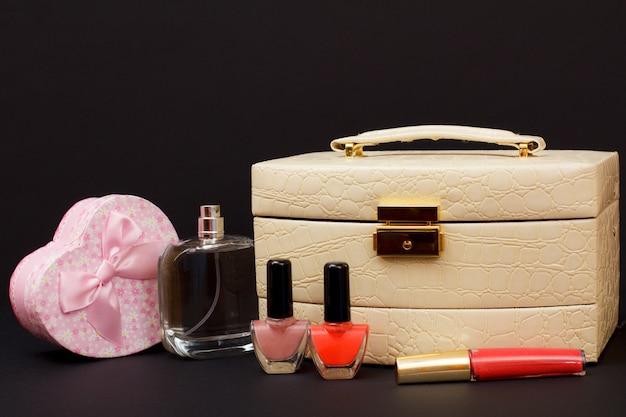 Cosmetische tas, parfum, nagellak, lippenstift en geschenkdoos in hartvorm op zwarte achtergrond. viering dag concept.
