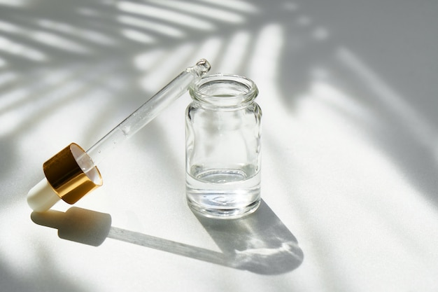 Cosmetische zeepbel met een druppelaar op een achtergrond van prachtige palmschaduwen mock up