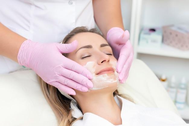 Cosmetologie. close-up foto van mooie jonge vrouw met gesloten ogen die gezichtsreinigingsprocedure in schoonheidssalon ontvangt.