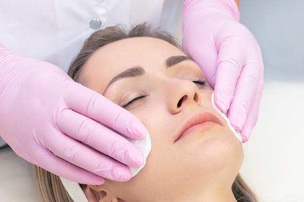 Cosmetologie. close-up foto van mooie jonge vrouw met gesloten ogen gezichtsreinigingsprocedure ontvangen in de schoonheidssalon.