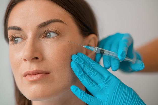 Cosmetologie. een donkerharige vrouw die schoonheidsbehandelingen ondergaat bij de cometologie