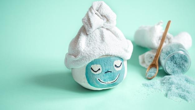 Cosmetologie, huidverzorging, gezichtsbehandeling, spa en natuurlijke schoonheidsconcept. kokosnoot met creatief gezichtsmasker en handdoek erop