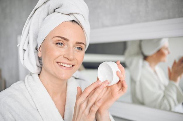 Cosmetologie, huidverzorging, gezichtsbehandeling, spa, natuurlijke schoonheidsconcept. mooie glimlachende vrouw thuis in badjas met een handdoek die gezicht bevochtigende room van witte kruik toepast. schoonheid routine