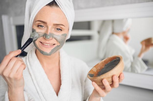 Cosmetologie, huidverzorging, gezichtsbehandeling, spa, natuurlijke schoonheidsconcept. mooie glimlachende vrouw thuis in badjas met een handdoek die het masker van de gezichtsklei toepassen tegen acne om probleemhuid te verjongen