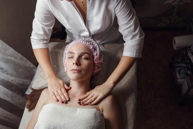 Cosmetologie kamer, schoonheidsspecialiste maakt gezichtsmassage aan een jonge mooie vrouw