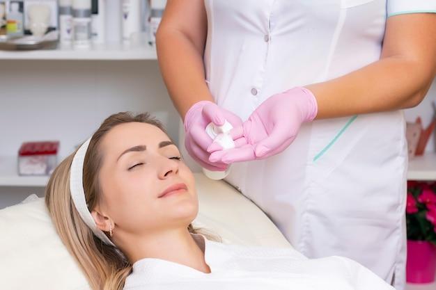 Cosmetologie. mooie jonge vrouw met gesloten ogen gezichtsreinigingsprocedure ontvangen in de schoonheidssalon.