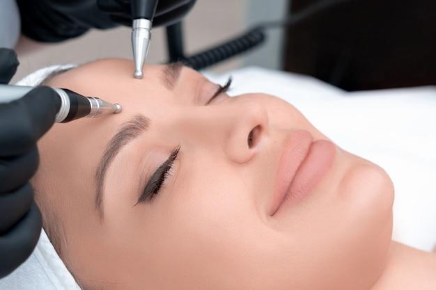 Cosmetologie. mooie vrouw die bij kuuroordkliniek stimulerende elektrische gezichtsbehandeling van therapeut ontvangen. close-up van jonge vrouwelijke gezicht tijdens microstroom therapie