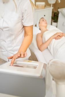Cosmetologie. mooie vrouw laser ontharing procedure ontvangen bij schoonheidssalon. schoonheidsspecialiste handen doen schoonheidsbehandeling voor vrouwelijk gezicht op spa salon.