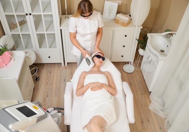 Cosmetologie. mooie vrouw laser ontharing procedure ontvangen bij schoonheidssalon.