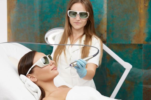 Cosmetologieprocedures in kliniek met mooie vrouw en schoonheidsspecialist met laserapparatuur