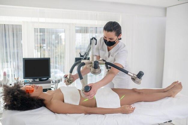 Cosmetologische procedure. glimlachend meisje in veiligheidsbril liggend op daybed en schoonheidsspecialiste staande laser apparaat instellen