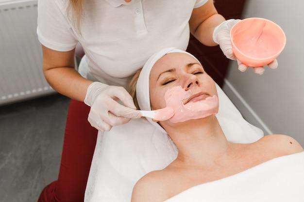 Cosmetologist brengt een masker op het gezicht van de cliënt aan