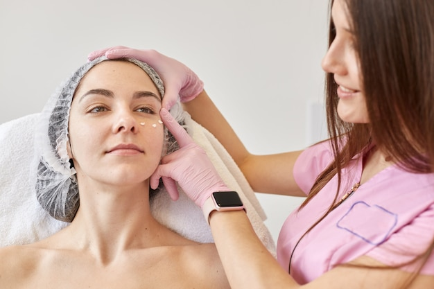 Cosmetologist brengt vochtinbrengende crème onder vrouwelijke ogen aan. portret van mooi meisje met medisch glb op hoofd over procedure in schoonheidssalon.