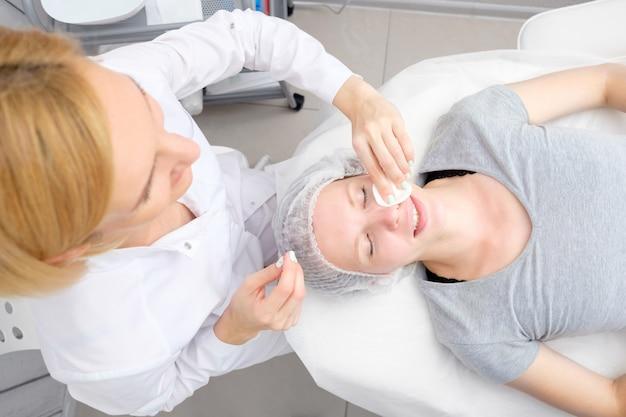 Cosmetologist die gezichtspeeling maakt