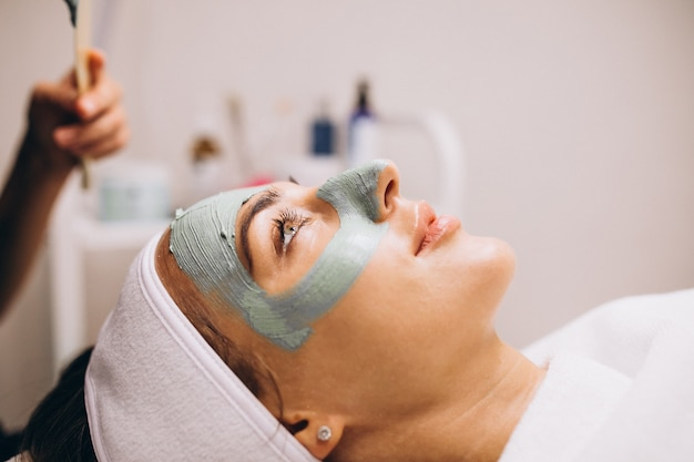 Cosmetologist die masker op een gezicht van cliënt toepast in een schoonheidssalon