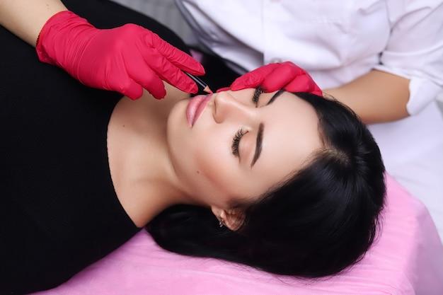 Cosmetologist die permanente make-up op het gezicht van de vrouw maakt