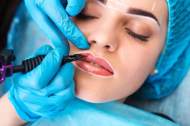 Cosmetologist die permanente make-up op vrouwengezicht maakt