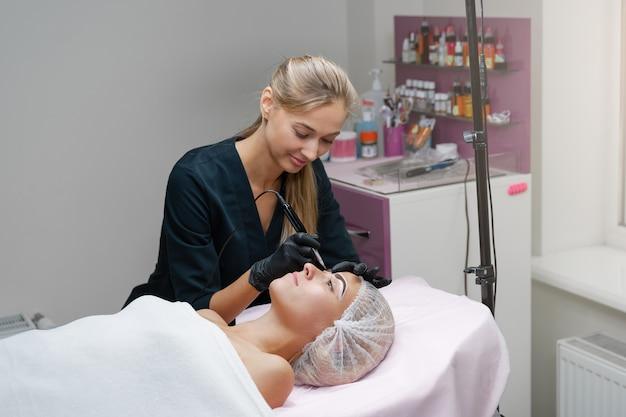 Cosmetologist die permanente make-up toepast
