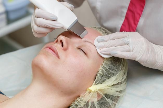 Cosmetologist die procedure doen om het gezicht met ultrasone scrubber schoon te maken