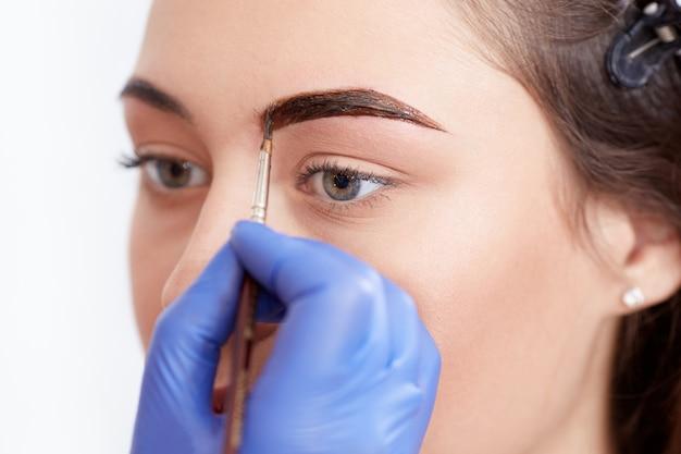Cosmetologist die speciale permanente samenstelling van wenkbrauwen toepast.