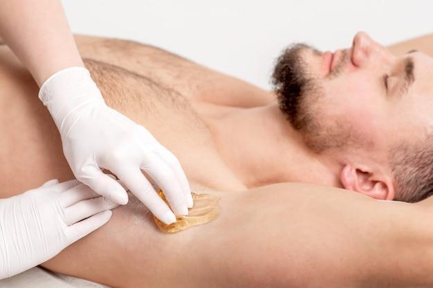 Cosmetologist die waspasta op mannelijke oksel toepassen