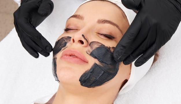 Cosmetologist die zwart masker op het gezicht van een mooie vrouw voor koolstofschil toepast