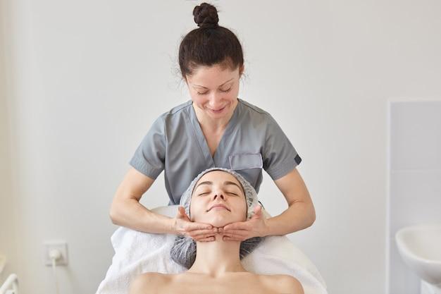 Cosmetologist draagt een grijze jurk die het gezicht van de patiënt masseert.