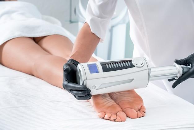Cosmetologist in rubberhandschoenen die endosferentherapie op vrouwelijke voeten doen