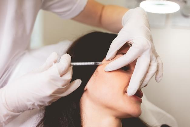 Cosmetologist maakt anti-aging injecties voor haar patiënt.