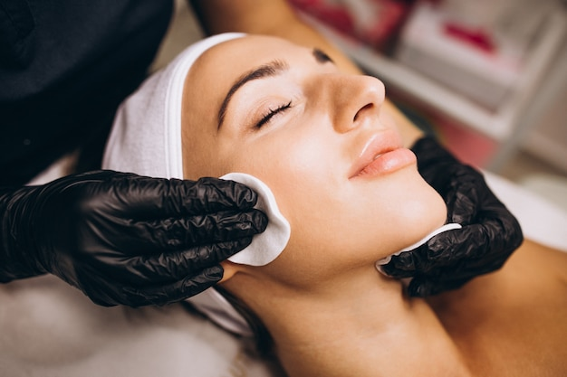 Cosmetologist schoonmakend gezicht van een vrouw in een schoonheidssalon
