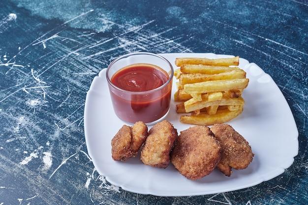 Cotlets met gebakken aardappelen en saus.
