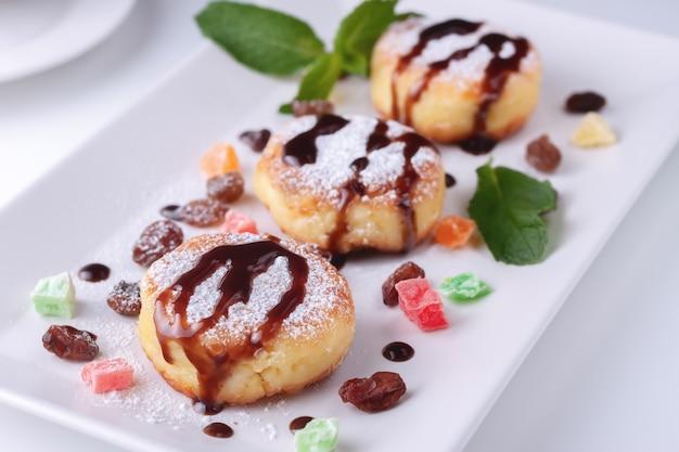 Cottage cheese pannenkoeken met rozijnen, gekonfijte vruchten en chocolade op een witte plaat bovenaanzicht