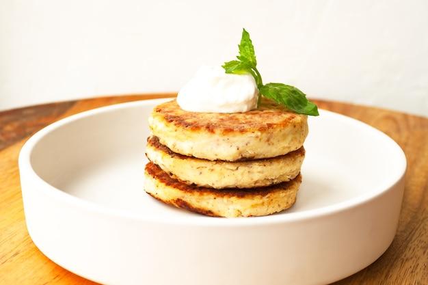 Cottage cheese pannenkoeken of gestremde beignets stapel met zure room munt versierd met amandel- en kokosmeel glutenvrij in witte plaat close-up. gezond eten ontbijt. selectieve zachte focus.