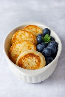 Cottage cheese pannenkoeken op een lichte achtergrond. syrniki met verse bosbessen. pannenkoeken met kwark op een witte schotel.