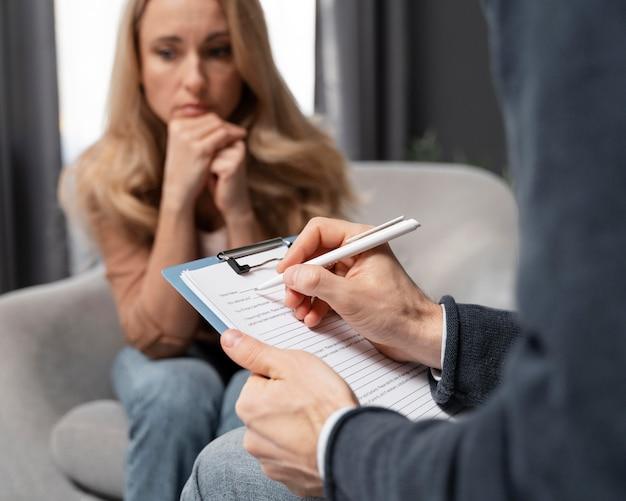 Counselor maakt aantekeningen naast vrouw