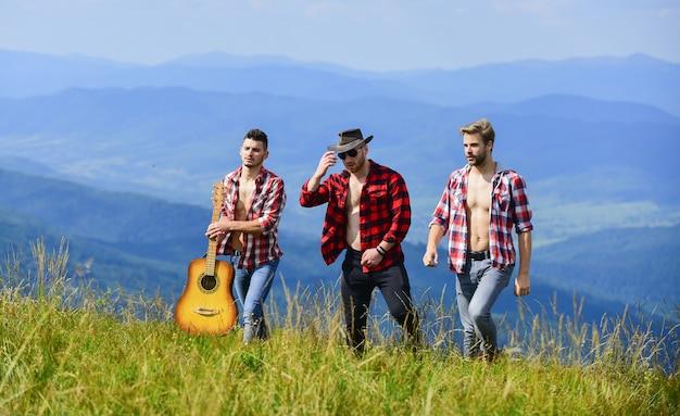 Country muziek. groep mensen brengen samen vrije tijd door. westerse camping. kampvuur liedjes. gelukkige mannen vrienden met gitaar. vriendschap. wandel avontuur. cowboymannen. mannen met gitaar in geruit overhemd.