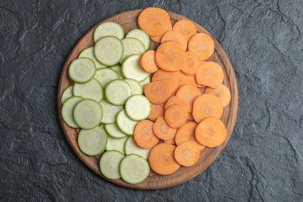 Courgette en wortelplakken in houten plaat op zwarte achtergrond. hoge kwaliteit foto