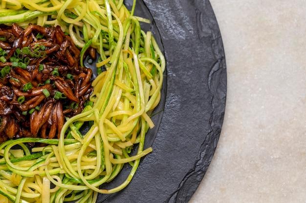 Courgette spaghetti met shimeji op zwarte stenen plaat