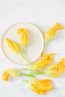 Courgettebloemen in een plaat op een lichte achtergrond