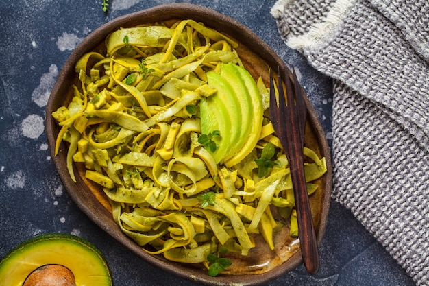 Courgettedeegwaren met pesto en avocado in donkere schotel. gezond veganistisch eten.
