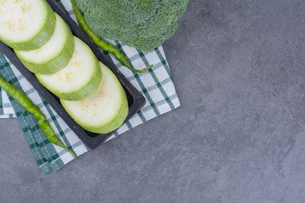 Courgetteschijfjes met broccoli en groene pepers op de grond